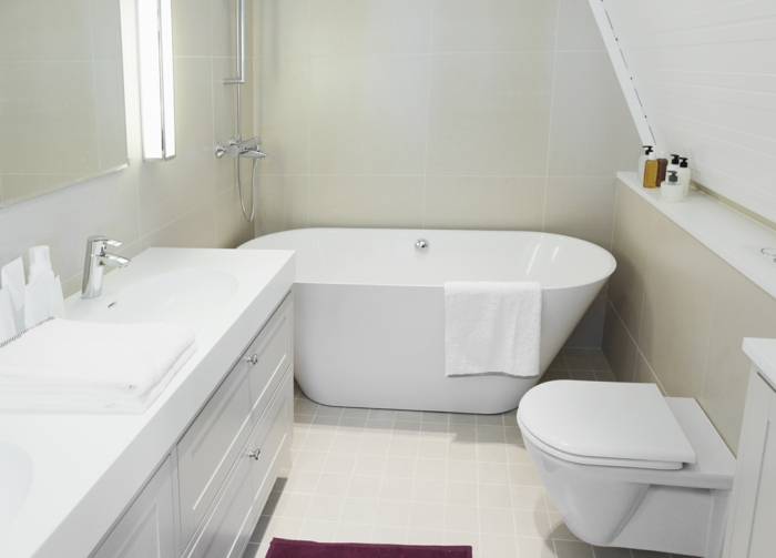 schöne Badezimmer in einer Dachwohnung, kleine Fliesen in weißer Farbe am Boden, ausgelassene Badewanne
