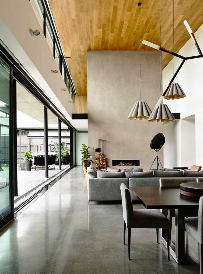 ein große Einzimmerwohnung mit beiger Raumteiler, hängende Pendellampen, ein graues Sofa