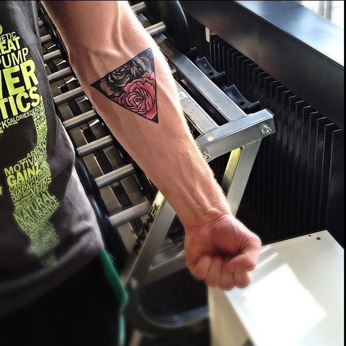 tattoos für männer, ein starker mann mit einer hand mit einem großen shcwarzen tattoo mit einem dreieck und schwarzen rosen und roten rosen tattoo, geometrische tattoos für männer