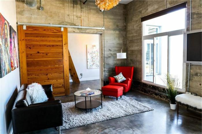 ein roter Sessel, ein schwarzes Sofa, ein grauer Teppich, Fußboden Betonoptik, ein Fernseher, ein großes Fenster
