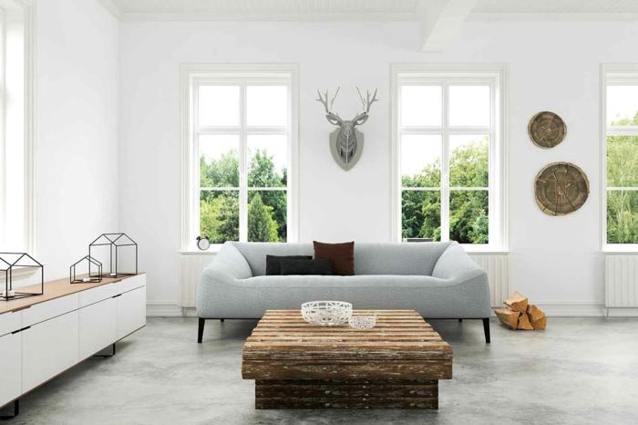 ein schlichtes Wohnzimmer, Hirschkopf an der Wand, ein Couchtisch aus Treibholz, graue Betonbodenfarbe