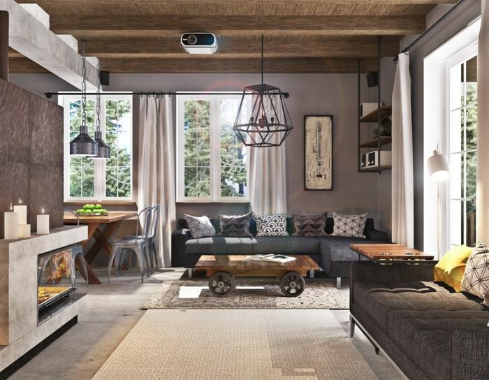 ein Tischlein mit Rädern, ausgefallener Lampenschirm und Pendellampen, graue Sofas, Betonbodenfarbe