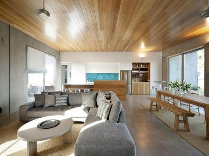 Betonbodenfarbe, ein graues Ecksofa, ein langer Esszimmertisch aus Holz mit Bank, die Küche ist im Hintergrund