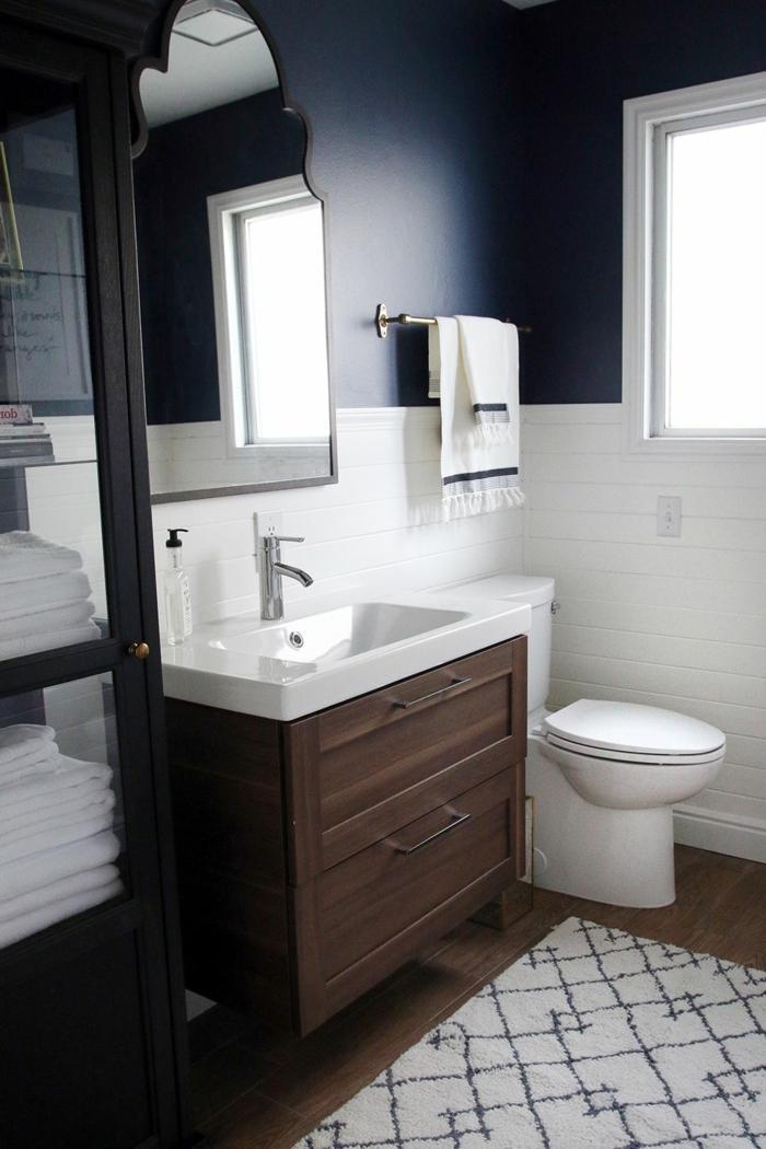 blaue Wände oben, Fliesen unten, Badezimmer Gestaltungsideen, kleiner weißer Teppich, Badmöbel Set aus Holz