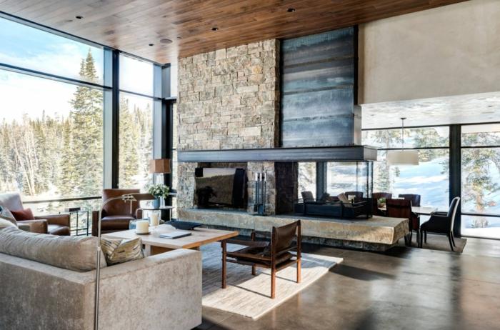 Betonbodenfarbe, ein Kamin in einem Ferienhaus im Gebirge, Sofa in beiger Farbe, Ledersessel