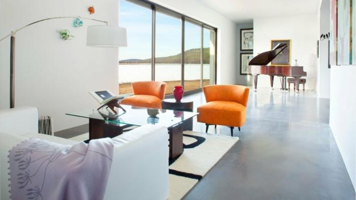 eine kleine Ferienwohnung, zwei orange Stühle, ein weißes Sofa, gläserner Tisch, Betonbodenfarbe