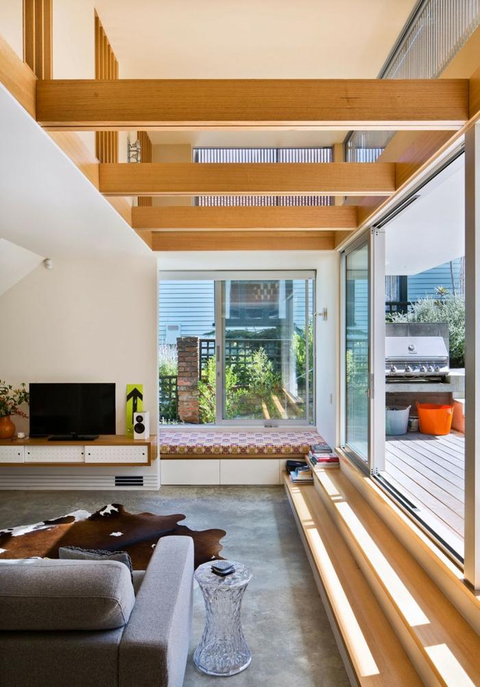 Betonbodenfarbe, eine Decke mit Balken, ein graues Sofa, ein gläsernes Tischlein, ein brauner Teppich