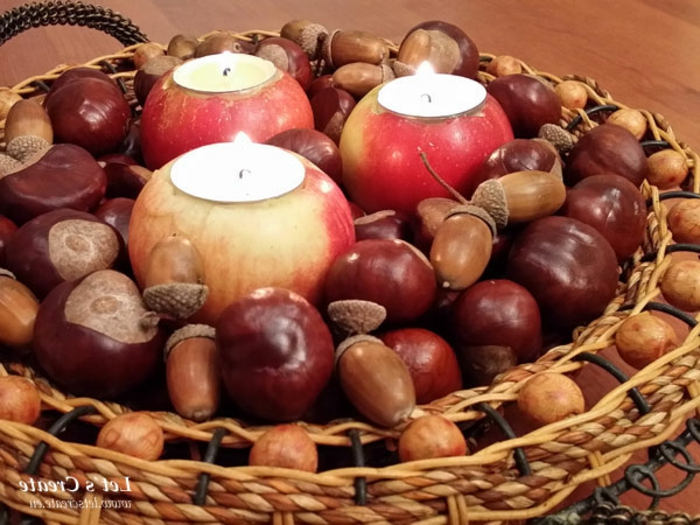 Kastanien Deko, ein Korb mit drei Äpfel, auf denen Teelichter stehen, Kastanien und Eichel