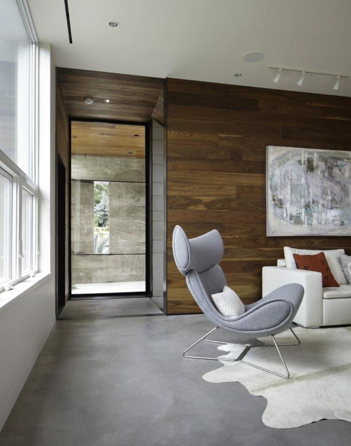 weißes Sofa, Betonbodenfarbe grau wie der Sessel, ein weißer Teppich, Wände mit hölzerner Verkleidung
