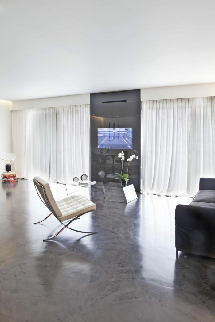 ein schlichtes Wohnzimmer mit Fernsehwand, ein beiger Stuhl und graues Sofa, polierter Beton