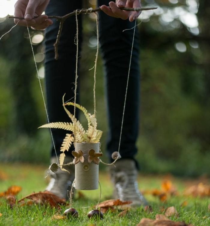 eine Drahtpuppe in der Hände von einem Mädchen, Gras als Haar, Kastanien als Beine, Kastanienfiguren