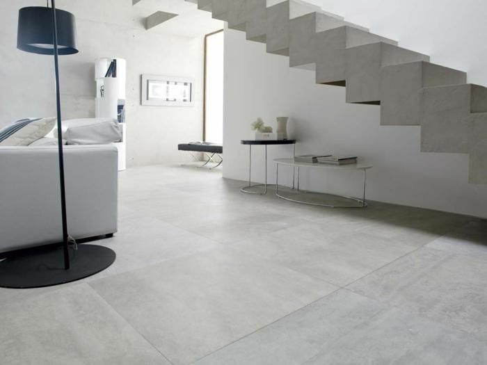 ein graues Treppenhaus, runde Tischleinen, ein weißes Sofa, eine schwarze Lampe, polierter Beton