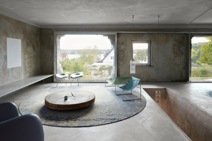 ein großes Fenster, ein grüner Liegestuhl und ein blauer Liegestuhl, ein runder Tisch und runder Teppich, polierter Beton