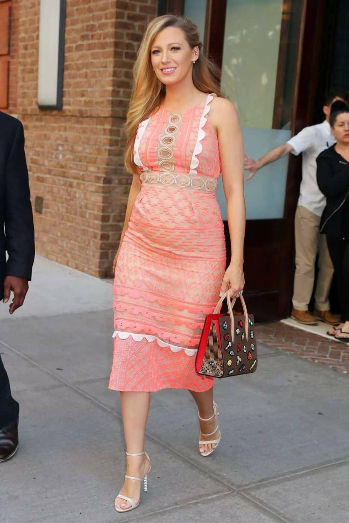 eine Prominente mit einem ausgefallenen Kleid, eine bunte Tasche, weiße Sandalen, Schwangerschaftsmode