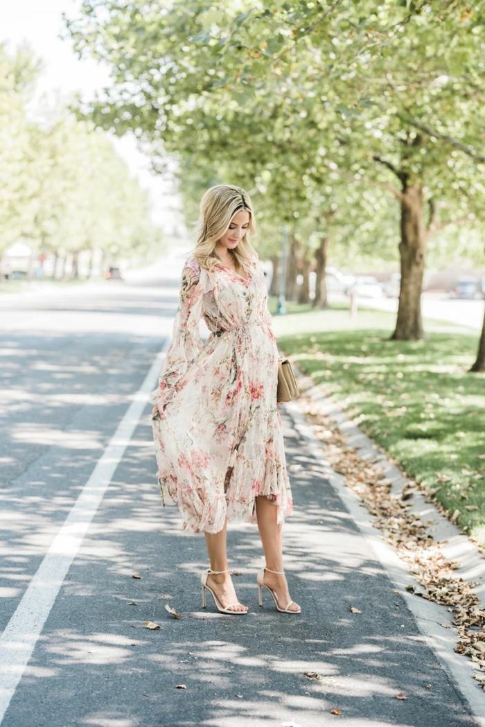 ein geblümtes Kleid, Schwangerschaftsmode, zwei beige Schuhe und beige Damentasche