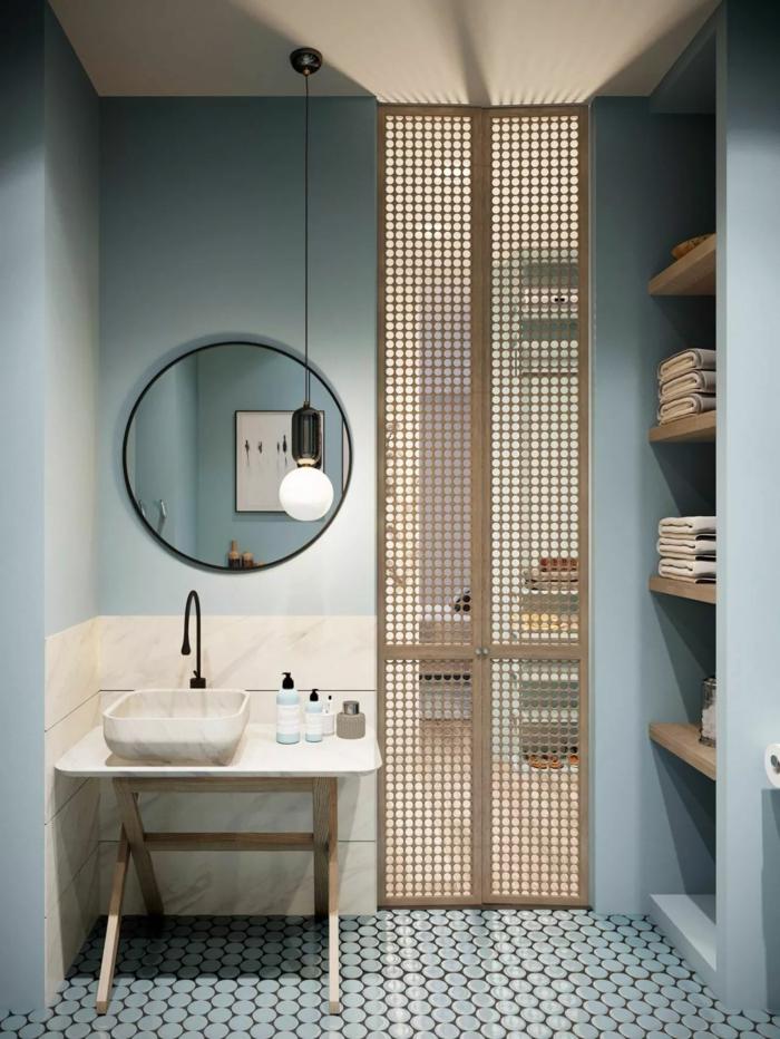 blaue Wände, ein runder Spiegel, kleine Mosaikfliesen, kleiner Abstelltisch mit Waschbecken, Badezimmer Ideen für kleine Bäder