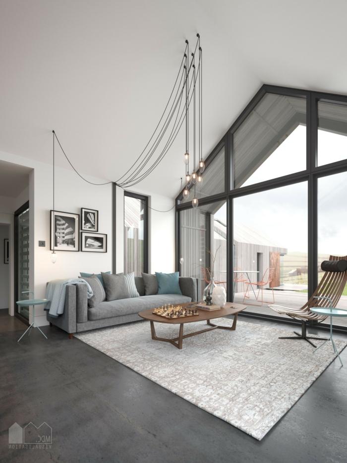 ein weißer Teppich, ein graues Sofa, hängende Glühbirne, ein brauner Liegestuhl, ein Fenster