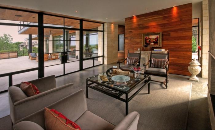 zwei Sessel und zwei Stühle, ein Couchtisch mit Dekorationen bedeckt, polierter Beton, indirekte Beleuchtung