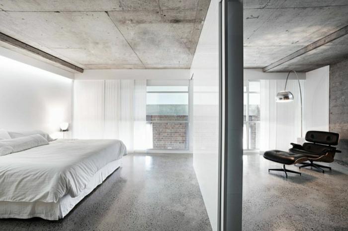 ein Schlafzimmer mit einem weißen Bett, polierter Beton, ein brauner Sessel in Leseecke, silberfarbene Lampe