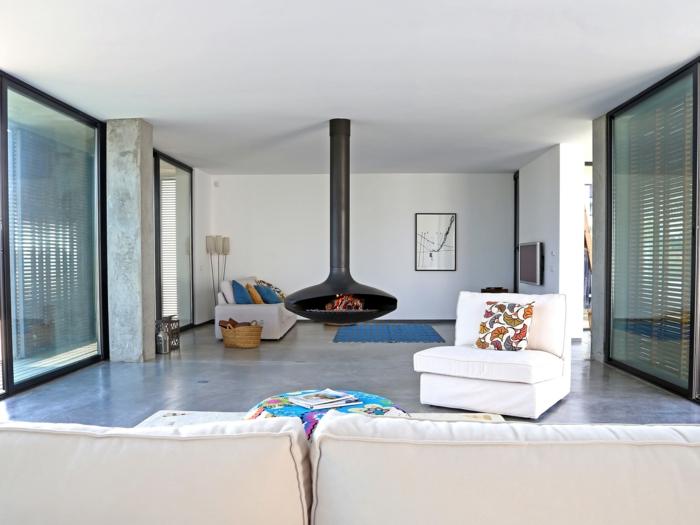 Bodenbelag Betonoptik, weiße Wohnzimmermöbel, ein weißes Bild, blauer Teppich, ein Herd