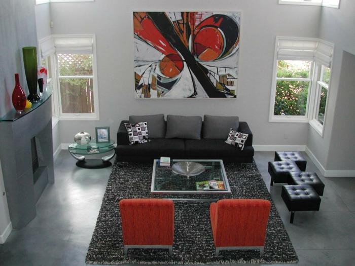 ein grauer Kamin, ein schwarzes Sofa, ein Bild un roter und schwarzer Farbe, Bodenbelag Betonoptik