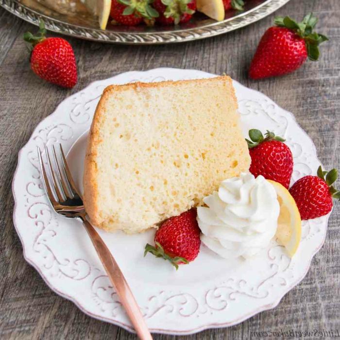 ein leckeres Stück Kuchen mit Erdbeeren und Sahne als Beilage in einem Teller