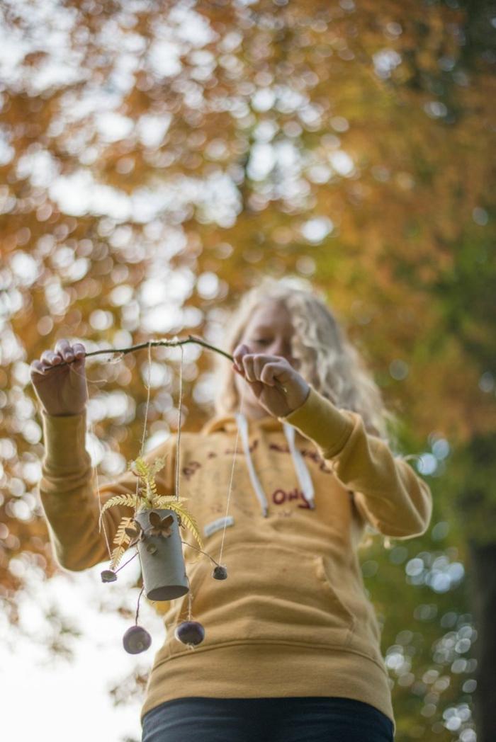 ein Mädchen mit gelber Bluse spielt mit der Drahtpuppe, die zu einem Zweig befestigt ist