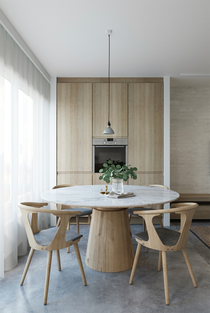 runder Tisch mit kleiner Vase als Dekoration, vier Stühle, eine Lampe darüber, Bodenbelag Betonoptik