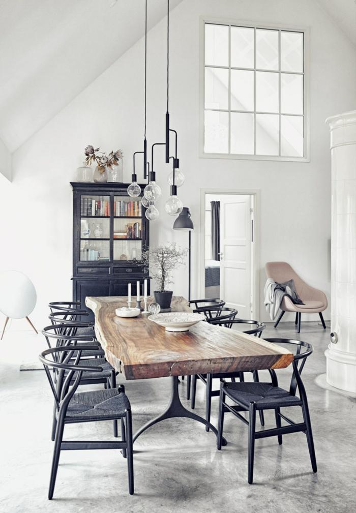 das Esszimmer in einer Dachwohnung, Tisch aus Holz, acht Stühle, Bodenbelag Beton