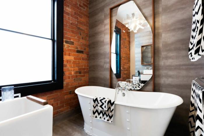 Badezimmer Gestaltungsideen, eine weiße Badewanne mit schwarz weißen Badeücher, Backstein Wand