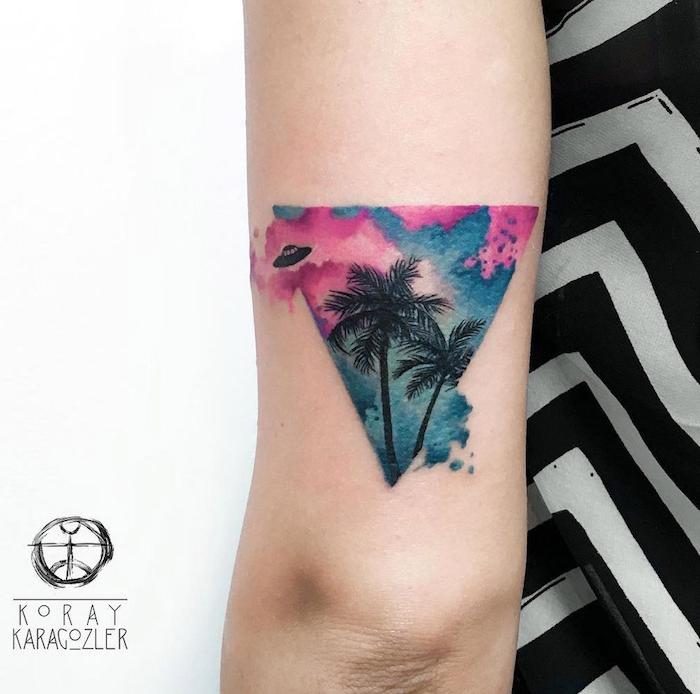 eine weiße wand und eine frau mit einem kleinen aquarell tattoo mit einem bunten dreieck und mit zwei schwarzen palmen, geometrische tattoos für frauen