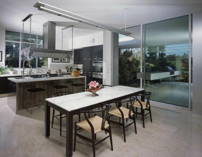 Esszimmer und offene Küche, Bodenbelag Betonoptik, Tisch in schwarz weiß und sechs Stühle