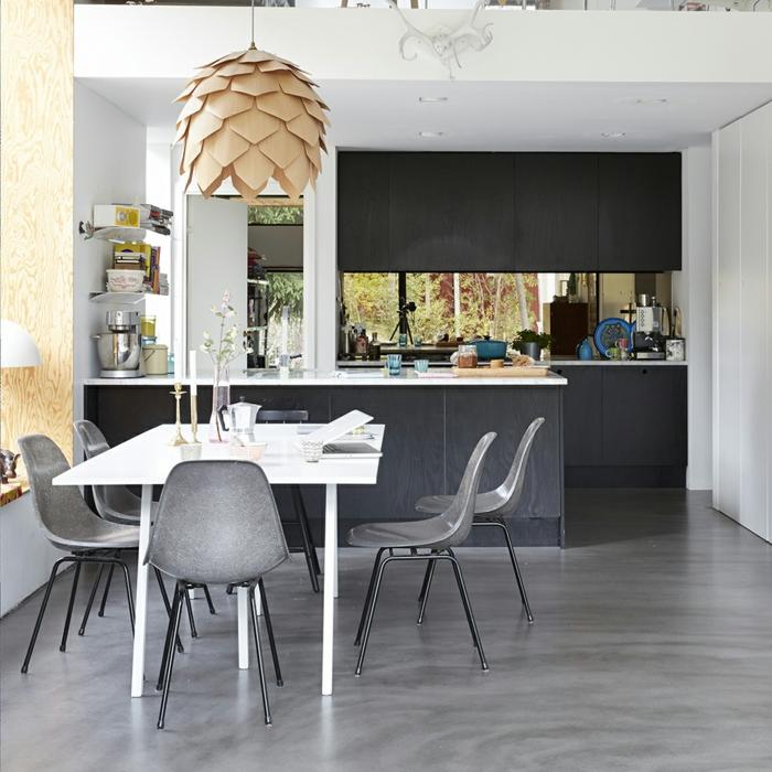 Esszimmer und offene Küche, weißer Tisch mit grauen Stühlen, Lampenschirm wie Zapfen, Bodenbelag Betonoptik