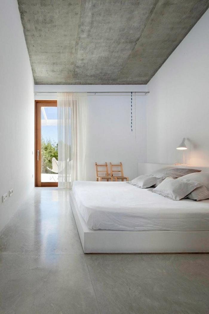 Bodenbelag Betonoptik im Schlafzimmer, ein weißes Bett, zwei kleine Stühle, eine Terrasse