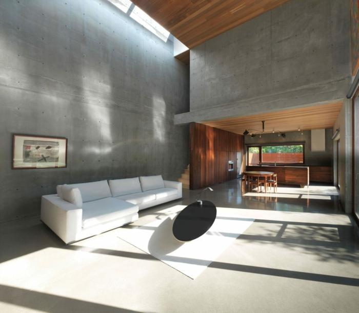ein Kontrast zwischen weißem Sofa und schwarzem Tisch, Wohnküche, Bodenbelag Betonoptik