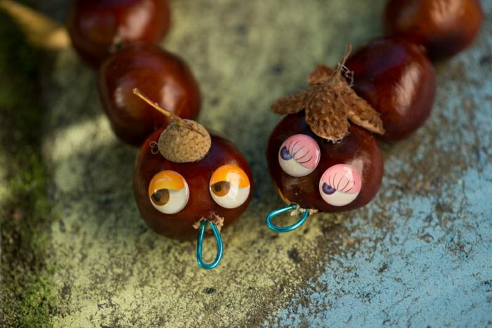 zwei Slange mit schönen Augen, kleine Mützen am Köpfchen, Bastelideen Herbst mit Kastanien und Fäden