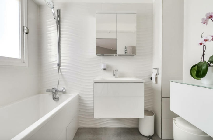 eine weiße Badewanne, Spiegelregal, weiße Unterschränke vom Waschbecken, schöne Badezimmer
