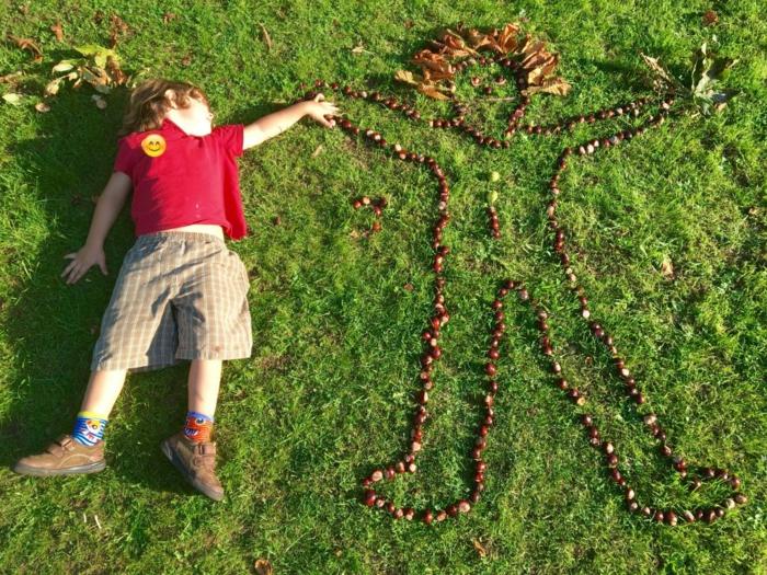 Kastanienfigur von einem Kind auf der Wiese, der Junge begrüßt einen Freund aus Kastanien