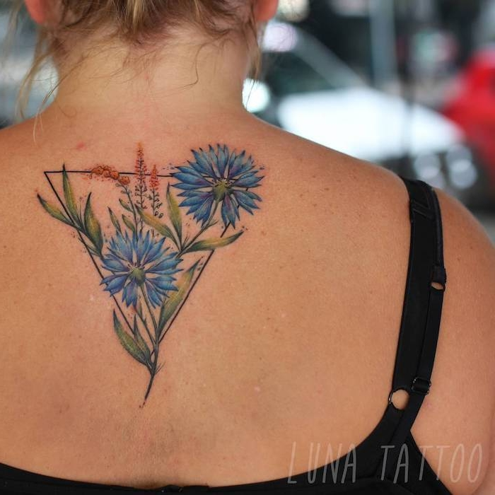 geometrische frauen tattoos, eine frau mit einem rücken mit einem großen watercolor tattoo mit einem dreieck und mit blauen blumen und grünen blättern