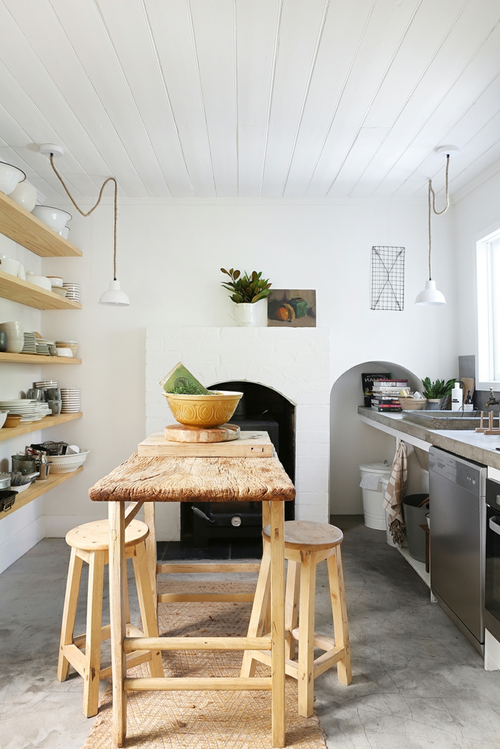 ein Tisch mit zwei Stühlen aus Holz, hölzerne Regale, weiße Decke, Betonfußboden, ein Kamin