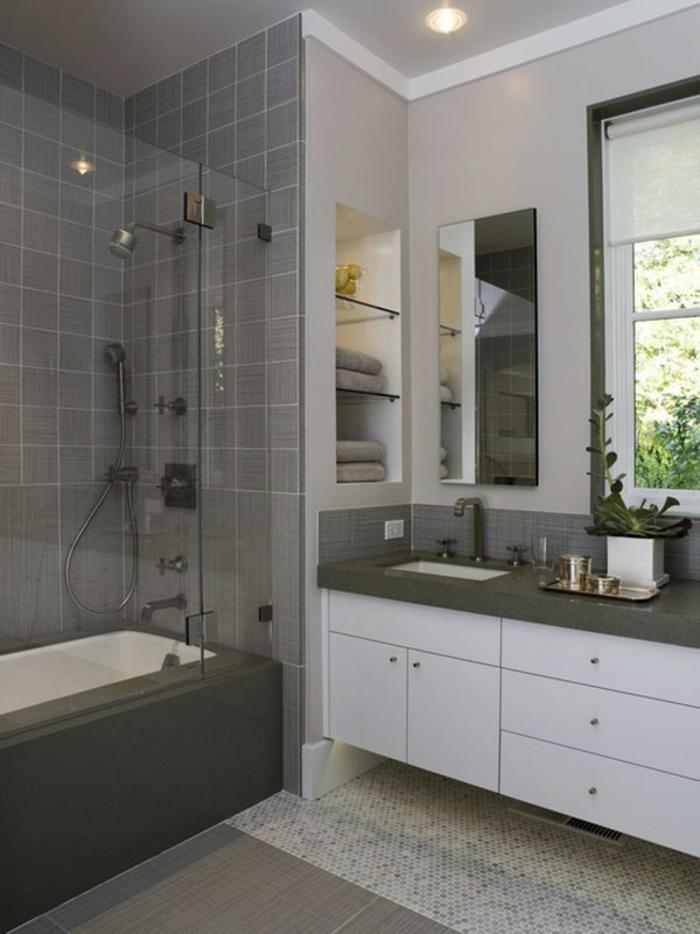 graue Fliesen an den Wänden, weiße Mosaikfliesen am Boden, ein Spiegel, schöne Badezimmer
