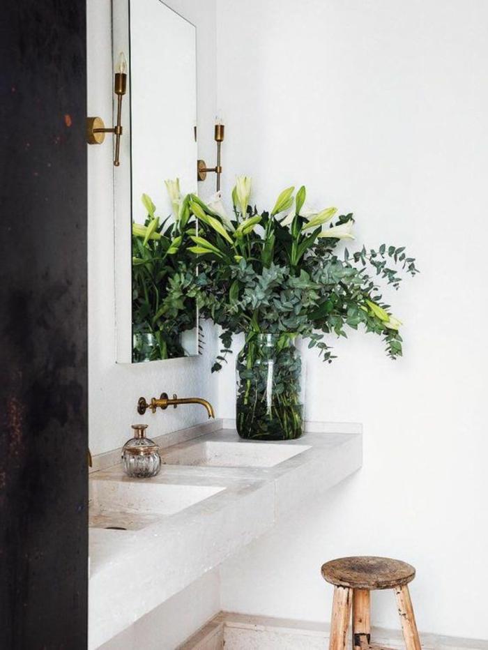 eine Vase mit vielen grünen Zweigen, ein quadrater Spiegel, ein Marmor Waschbecken, ein niedriger Stuhl, Badezimmer Ideen für kleine Bäder