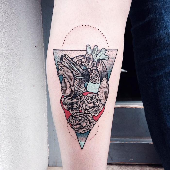eine weiße wand und eine hand mit einem großen bunten tattoo mit einem dreieck und mit einem herzen und drei weißen rosen