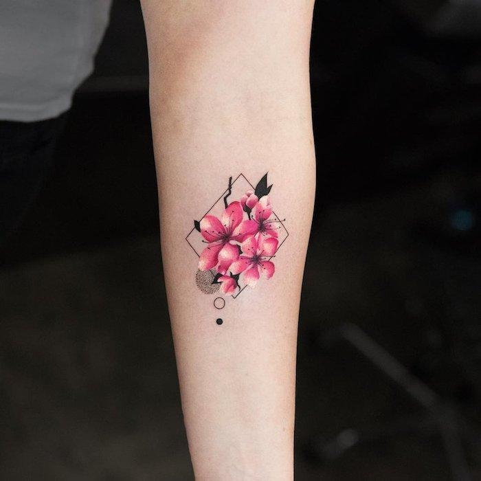 frauen tattoos motive, eine hand mit einem kleinen tattoo aquarell mit kleinen pinken blumen und schwarzen blättern und geometrischen formen, watercolor painting