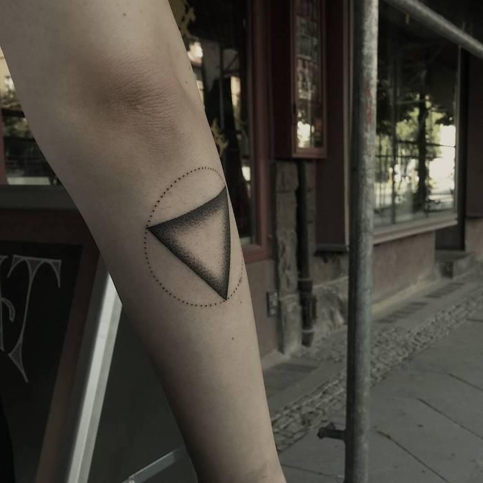tattoo ideen für männer, eine hand mit einem kleinen schwarzen tattoo mit einem schwarzen dreieck und mit einem kreis, geometrische tattoos ideen