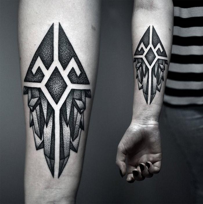 frauen tattoos ideen, eine hand einer frau mit einem schwarzen nagellack und mit einem tattoo mit zwei schwarzen flügeln mit schwarzen federn, tattoo ideen für frauen, tattoos mit geometrischen formen