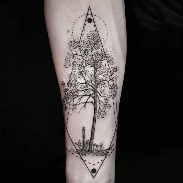eine hand mit einem großen schwarzen tattoo mit einem schwarzen baum mit schwarzen blättern, grass und, eine sonne und mond, geometrische tattoos ideen