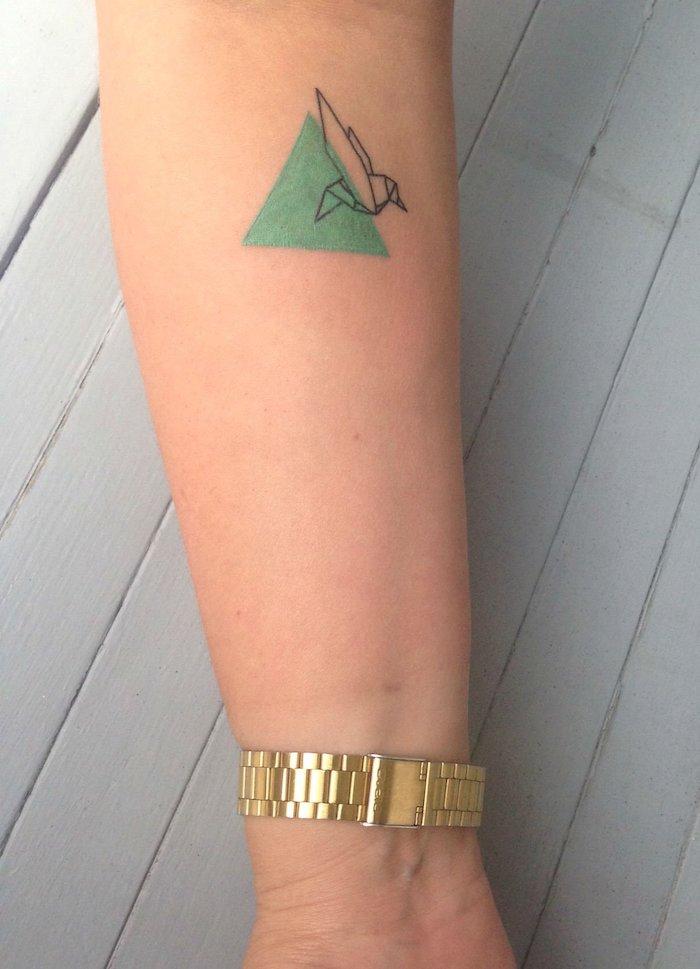 ein weißer tisch aus holz und eine hand mit einer goldenen uhr, eine hand mit einem aquarell tattoo mit einem grünen dreieck und mit einem fliegenden vogel