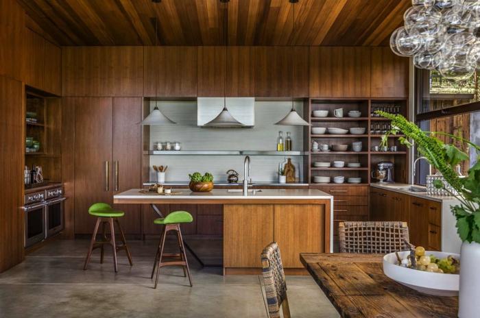 Regale voller Teller und Schalen, hängende Pendelleuchten, Kochinsel mit grünen Hockern, Boden Betonoptik