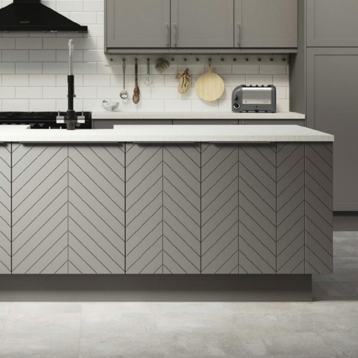 eine weiße Wand in Backstein Optik, graue Schränke, Kochinsel mit geometrischen Mustern